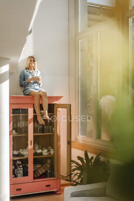 Woman sitting on cupboard with coffee — Stock Photo