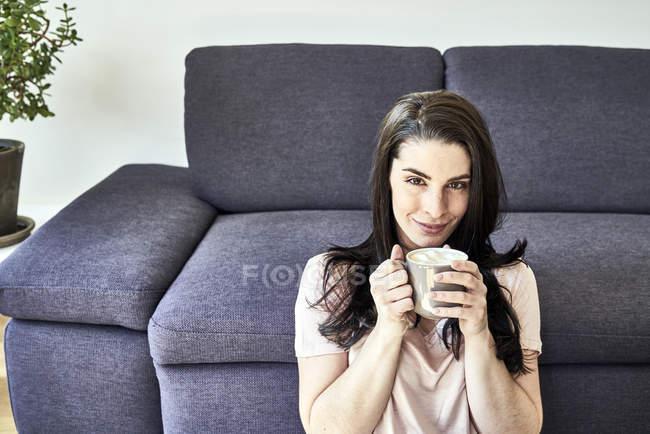 Woman sitting with coffee mug — Stock Photo