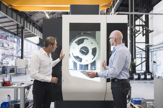 Men discussing on factory shop floor — Stock Photo