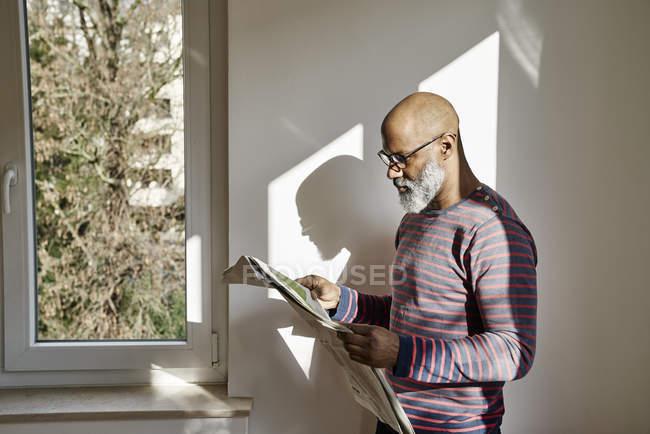 Зрілою людиною, читаючи газету біля вікна — стокове фото