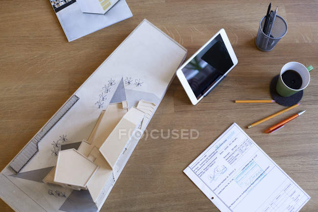 Desk with tablet and architectural model — Stock Photo
