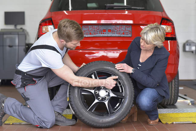 Car mechanic and client crouching with tyre — Stock Photo