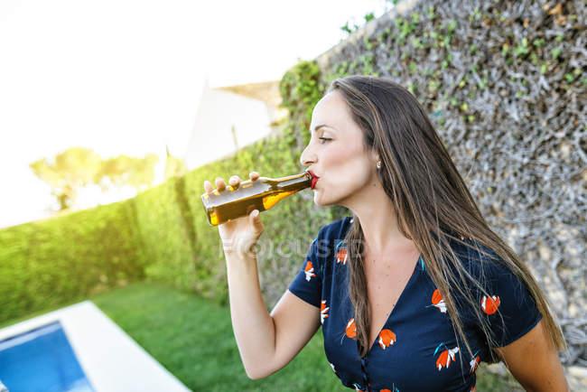 Жінка п'є пиво в біля басейну — стокове фото