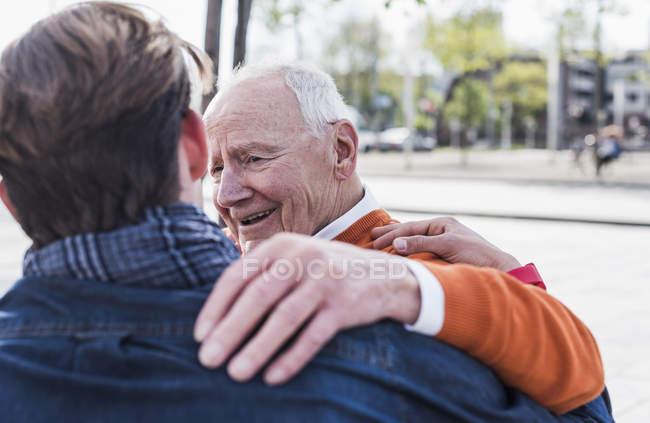 Senior man and grandson sitting outdoors — Stock Photo