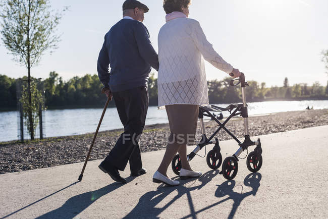 Senior couple strolling near river — Stock Photo