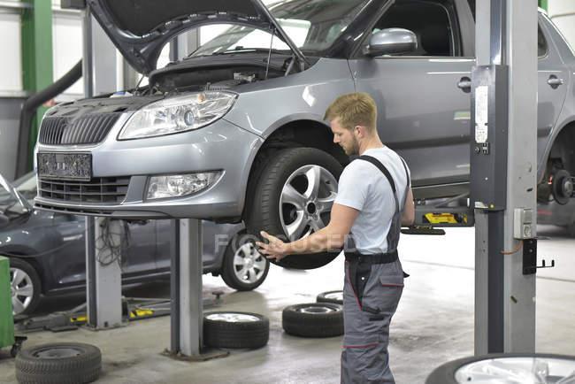 Car mechanic changing tyre — Stock Photo