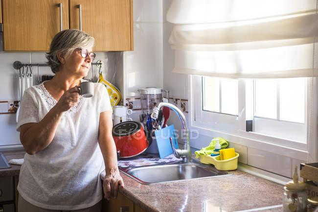 Mujer mayor con taza de café - foto de stock