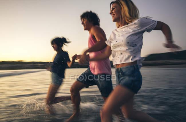 Щасливі друзів, тримаючись за руки і біг до моря в сутінках — стокове фото
