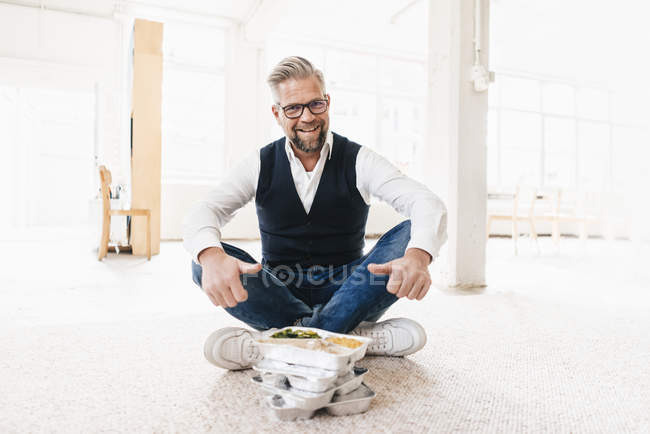 Businessman sitting with take away food — Stock Photo