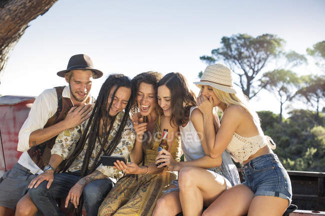 Happy young people sitting near van and sharing cell phone — Stock Photo