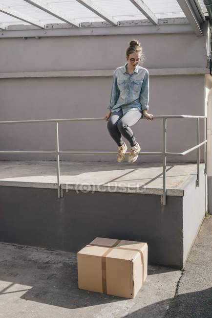 Woman about to jump on cardboard box — Stock Photo