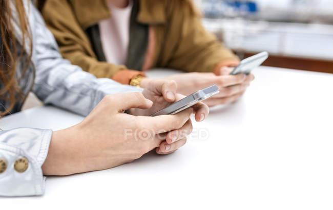 Две женщины, использующие смартфоны — стоковое фото