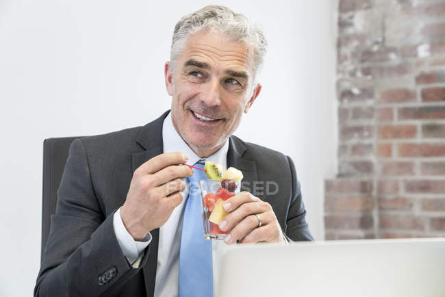 Businessman eating fruit salad — Stock Photo