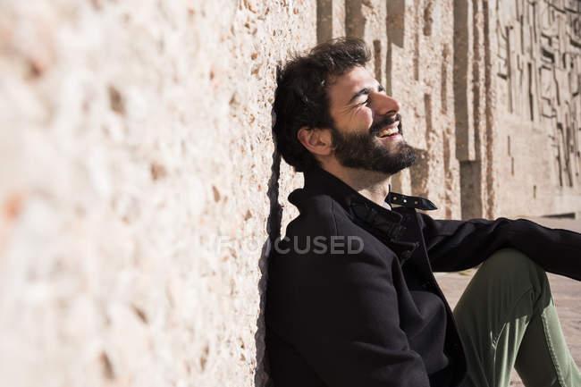 Homem com os olhos fechados encostados na parede — Fotografia de Stock