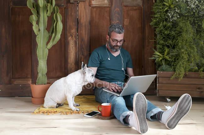Bärtiger Mann sitzt mit seinem Hund — Stockfoto
