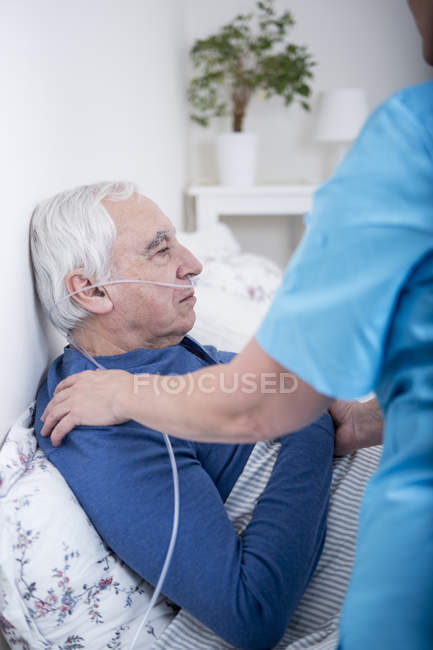 Nurse helping patient with nasal tubes — Stock Photo