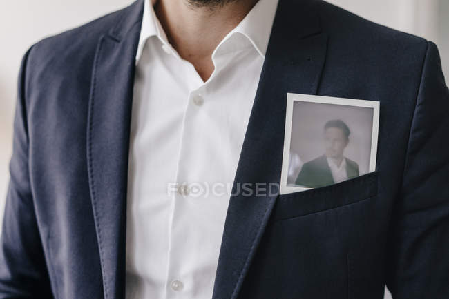 Businessman with instant photo in pocket — Stock Photo