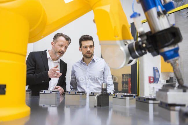 Two businessmen observing industrial robots — Stock Photo