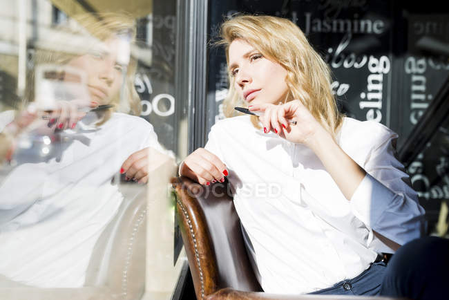 Woman in cafe looking out of window — Stock Photo