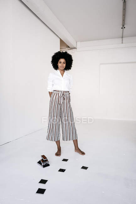 Woman with instant camera on floor — Stock Photo