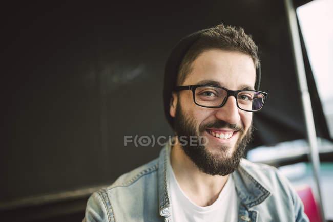 Uomo barbuto indossando occhiali e cappello — Foto stock