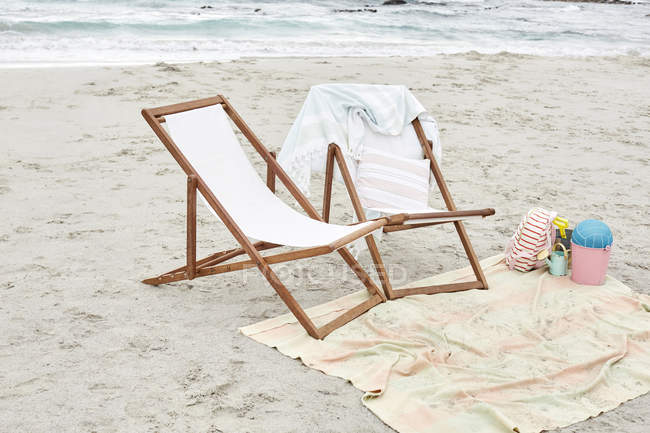 Empty sun loungers on beach — Stock Photo