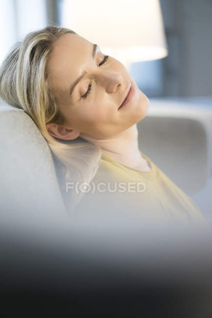 Blond woman relaxing on couch — Stock Photo