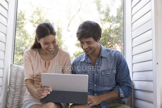 Paar auf der Fensterbank sitzen und mit tablet — Stockfoto
