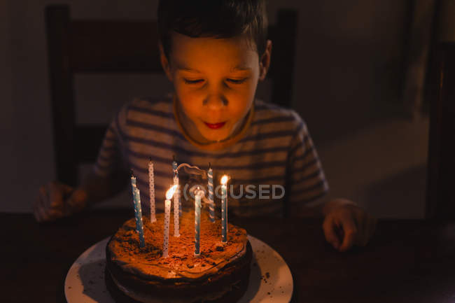 Boy blowing with birthday cake — Stock Photo