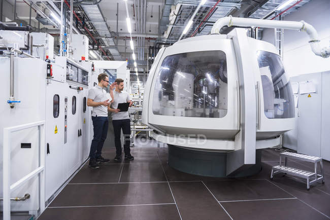 Two men talking at machine — Stock Photo