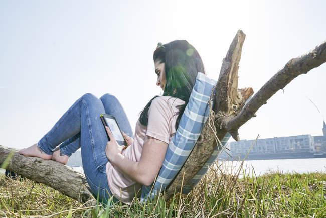 Женщина отдыхает на газоне и с помощью планшета — стоковое фото