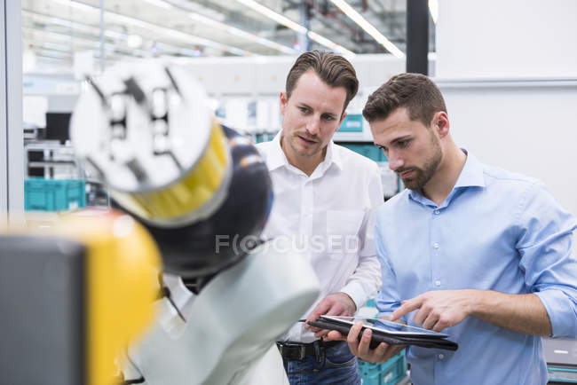 Men with tablet examining assembly robot — Stock Photo