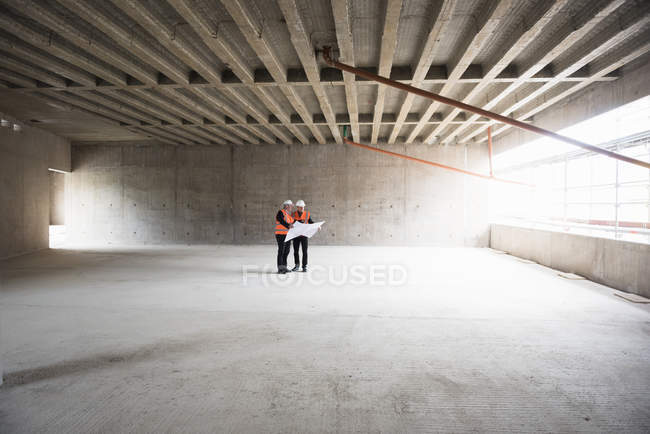 Men interacting in building under construction — Stock Photo
