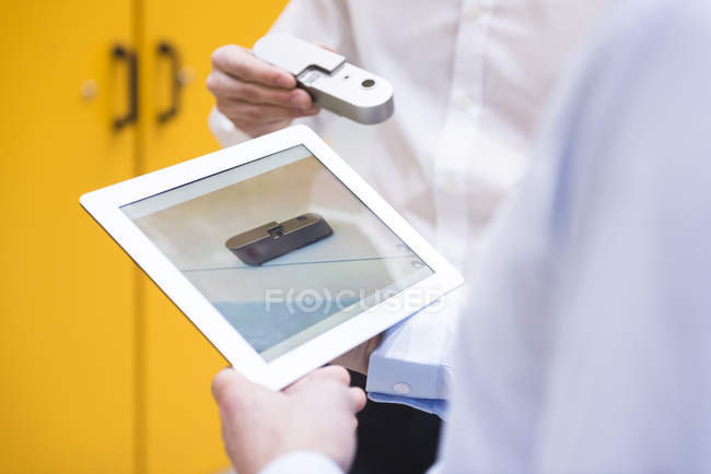 Hands examining product with tablet — Stock Photo