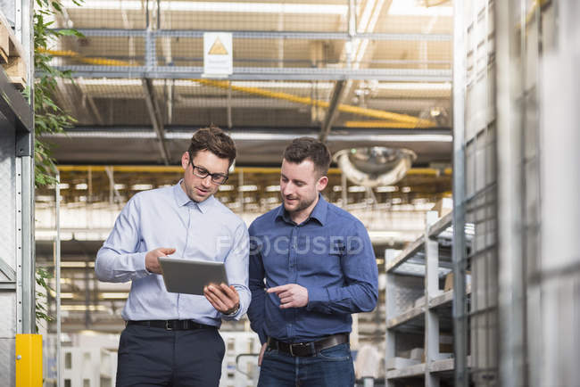 Men with tablet talking in factory — Stock Photo