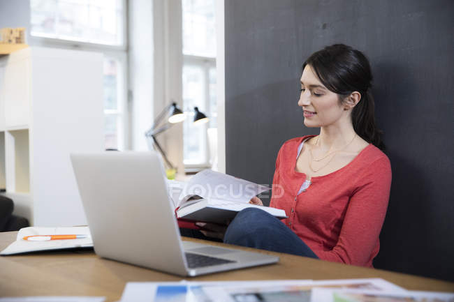 Woman with book and laptop — Stock Photo