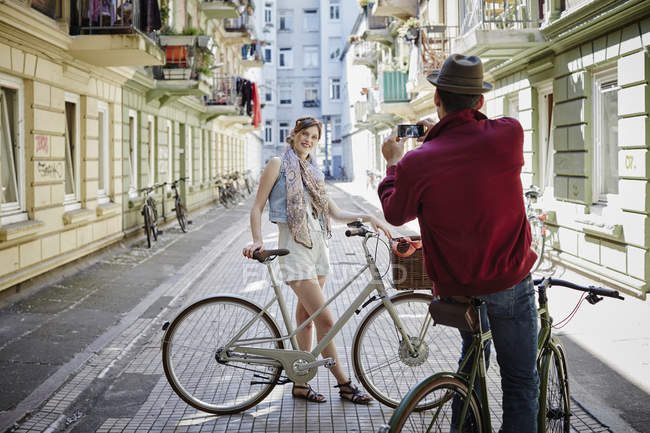 Germany, Hamburg, St. Pauli, Man taking picture of woman with bicycle — Stock Photo