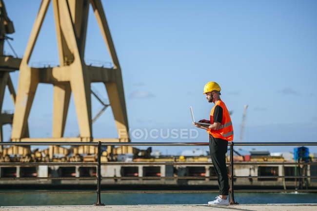 Trabalhador portuário usando um laptop — Fotografia de Stock