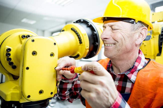 Técnico sonriente trabajando en robot industrial - foto de stock