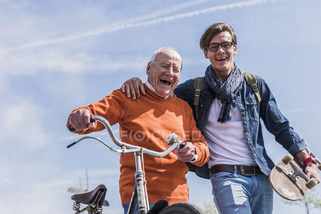 Senior homme avec vélo et petit-fils avec planche à roulettes — Photo de stock