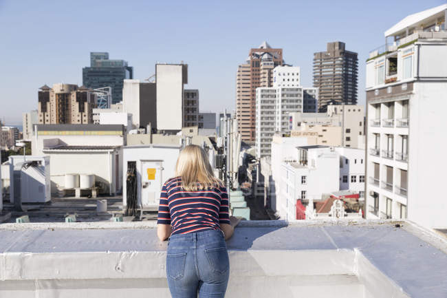 Woman looking from rooftop terrace — Stock Photo