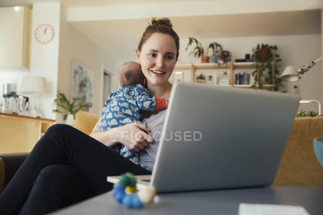 Мати за допомогою ноутбука і проведення її дитини — стокове фото