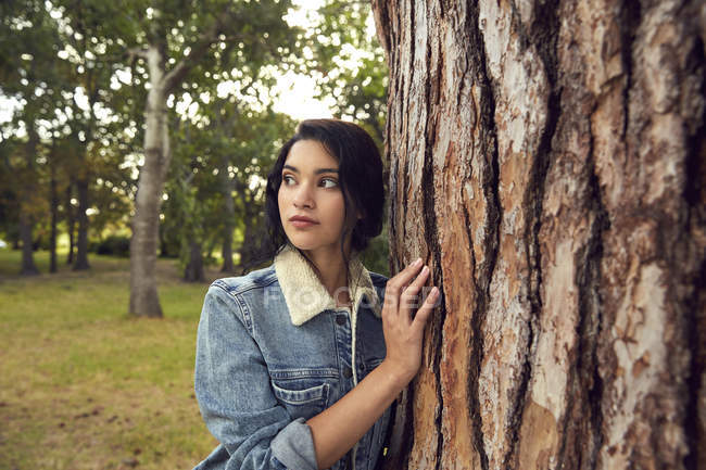 Young woman leaning against tree — Stock Photo