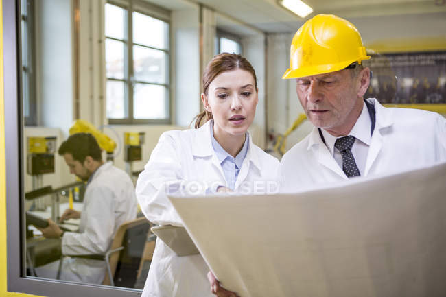 Two engineers in factory looking at plan — Stock Photo