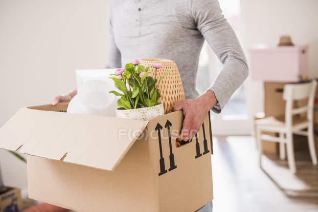 Ritratto ritagliato di giovane uomo che trasporta scatola di cartone — Foto stock