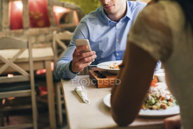 Uomo che controlla i messaggi nel ristorante — Foto stock