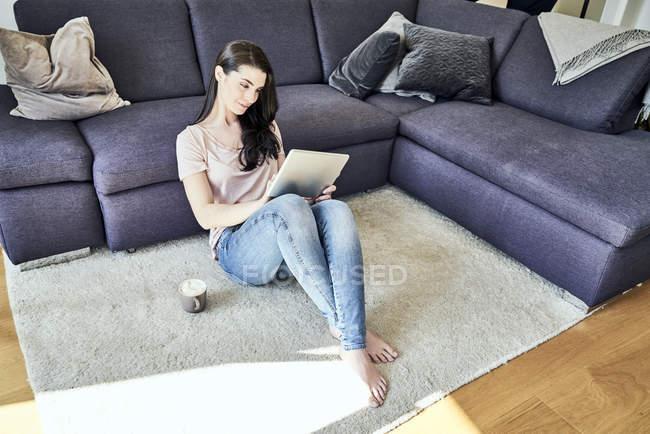 Donna che usando la tavoletta al piano — Foto stock