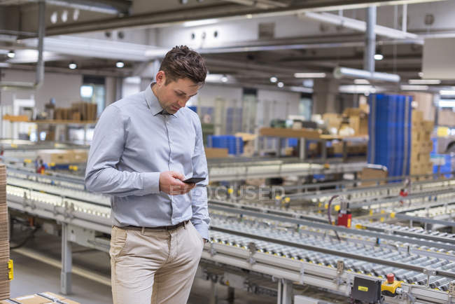 Man at conveyor belt in factory looking at cell phone — Stock Photo