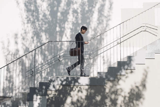 Young man in suit walking on stairs and looking at cell phone — Stock Photo