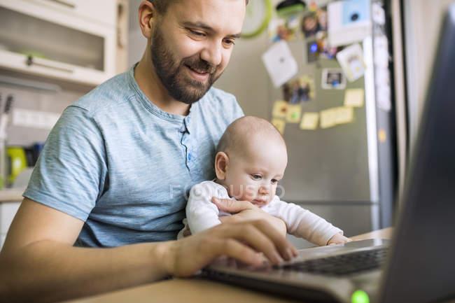 Отец с маленьким сыном с помощью ноутбука — стоковое фото
